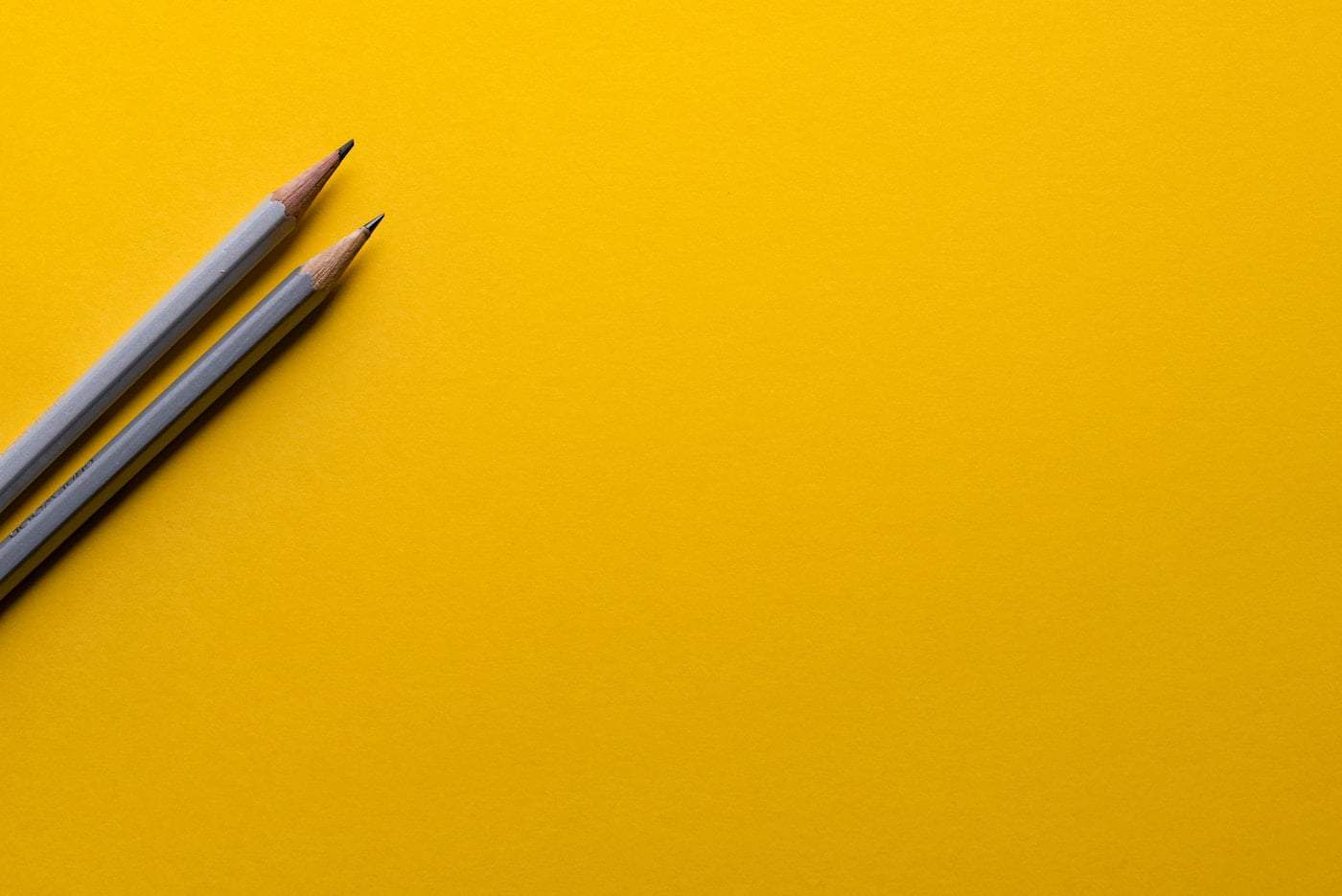 Pencils on yellow background symbolising Health & Education Co-Operative